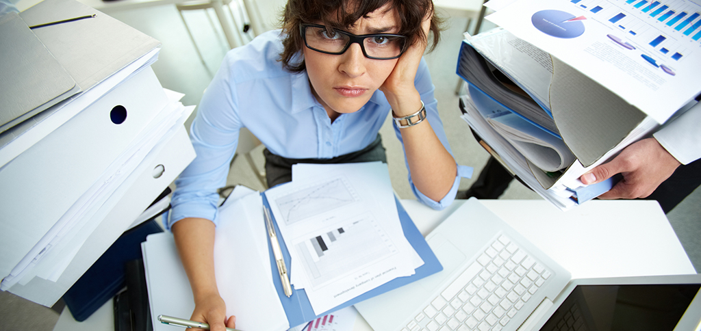 Woman working too hard in an office with files and paperwork all over her desk.