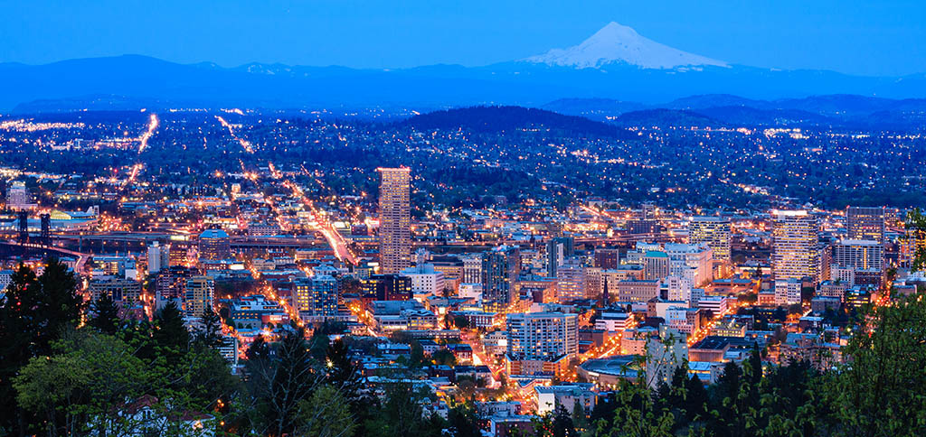 Portland Oregon metro glows with light at dusk while Mount Hood watches over