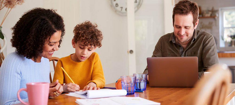 Father Works On Laptop As Mother Helps Son With Homework On Kitchen Table to demonstrate ability to work from home