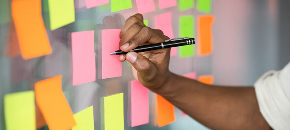 man organizing post-it notes on an office wall